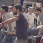 Civilians Carry Wounded Out of the Crowd